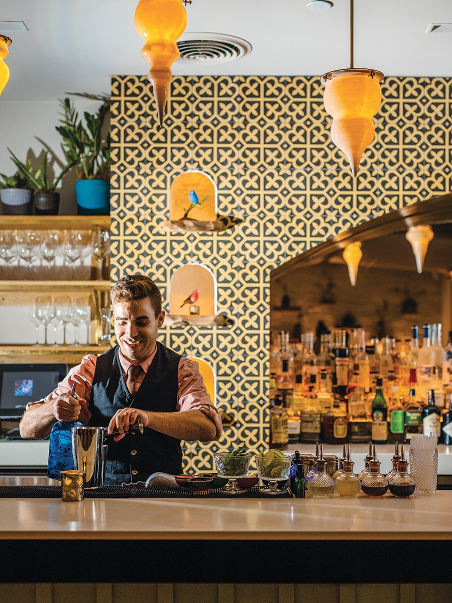 An enthusiastic bartender mixing a cocktail.