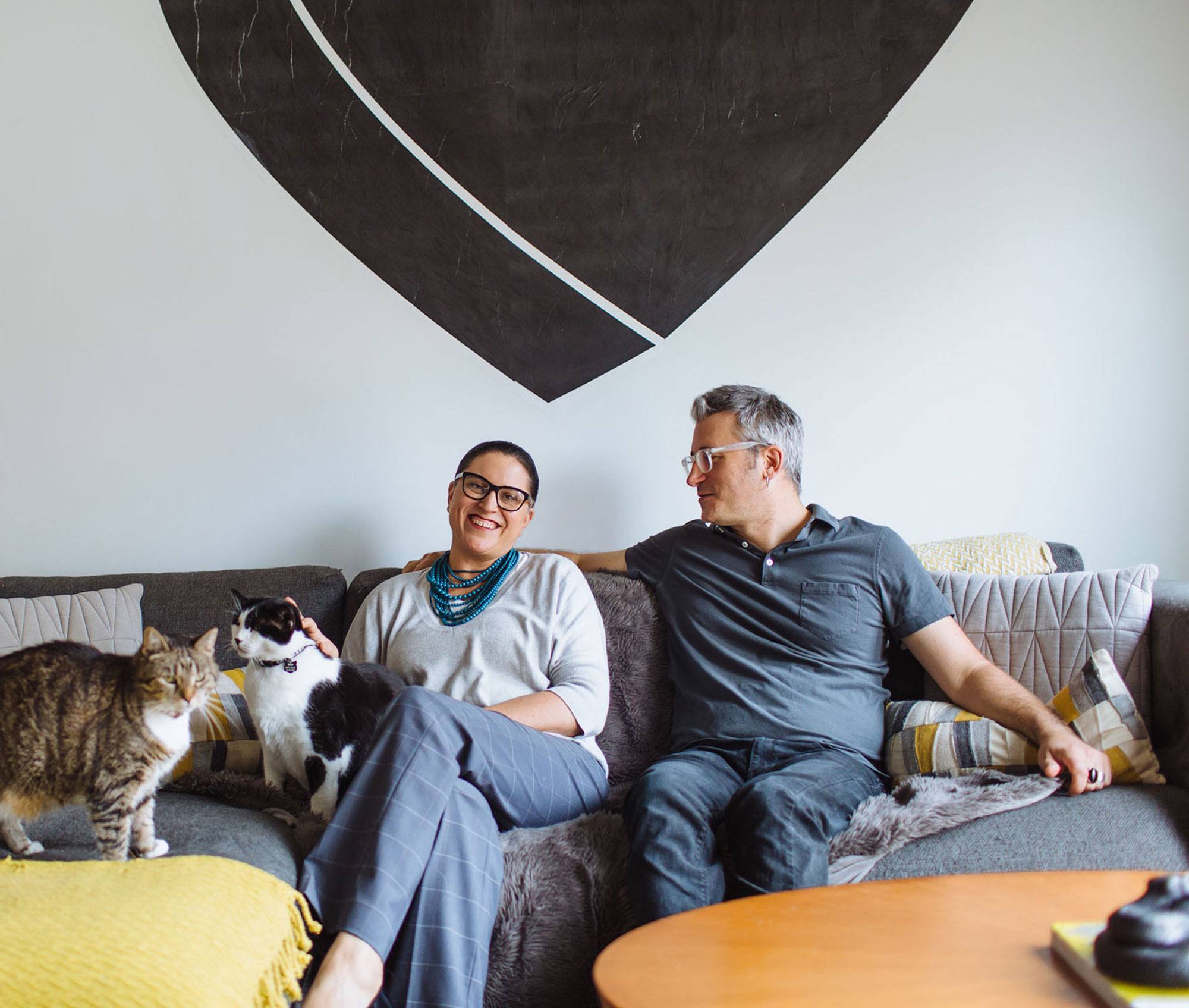 Two people sitting on a couch with a dog and a cat.