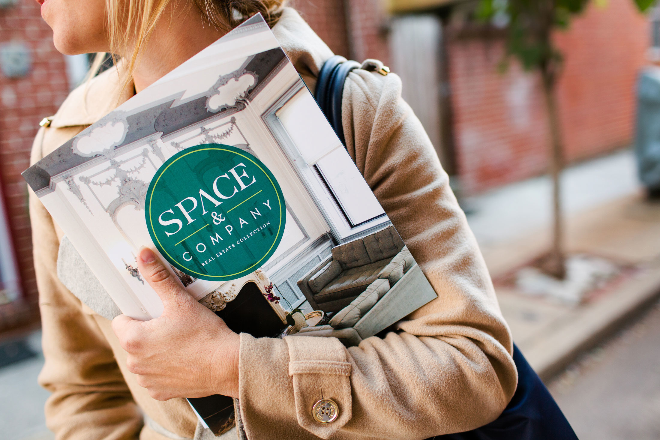 Space & Company agent holding real estate literature.